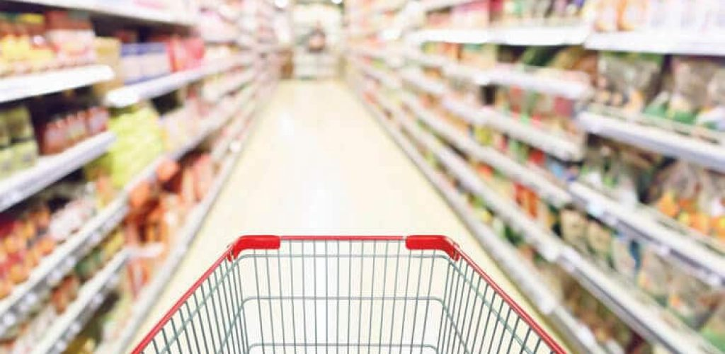 Abstract blur supermarket aisle with can food and snack product on shelves defocused background