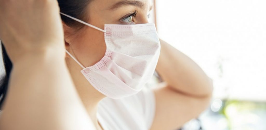 Woman puts on mask that protect from bacteria and viruses