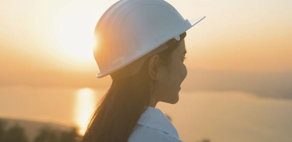 a woman engineer is putting a protective helmet on her head at sunset.
