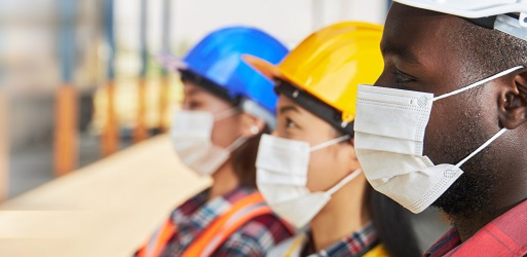 Portrait of industrial workers wearing surgical masks, standing on top of together in layers within the factory.