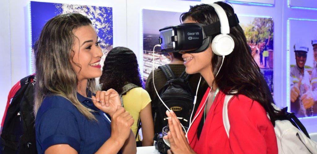 Voluntária da Alumar apresentando o óculos virtual para visitante