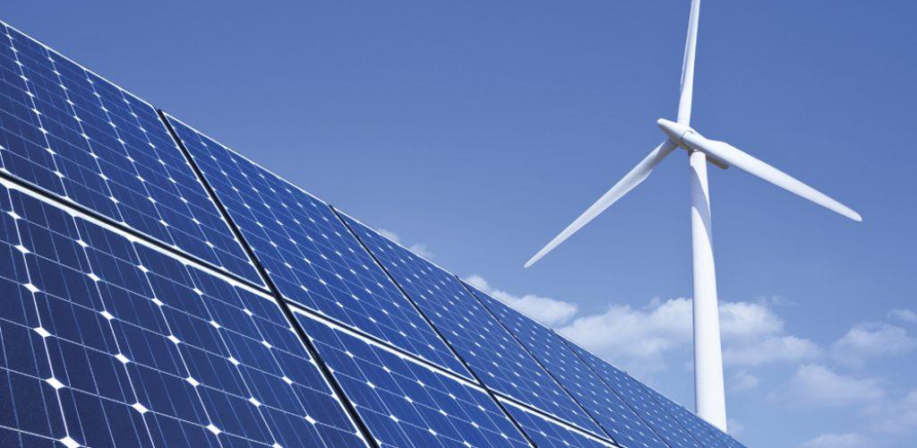 Solar panels and wind turbine against blue sky